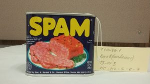 This is a front shot of the Spam Bank with its description label standing next to it.