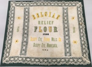 "photo of an embroidered flour sack, bordered with lace. It reads: ""BELGIAN / RELIEF / FLOUR / FROM / SLEEPY EYE FLOUR MILLS CO. / SLEEPY EYE, MINNESOTA / 1914 / 1915"""